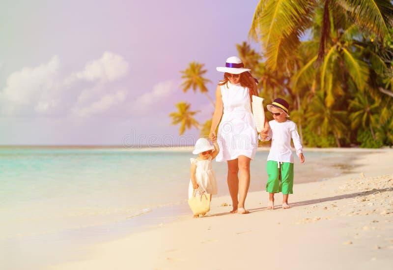 Moeder en twee jonge geitjes die op tropisch strand lopen stock fotografie
