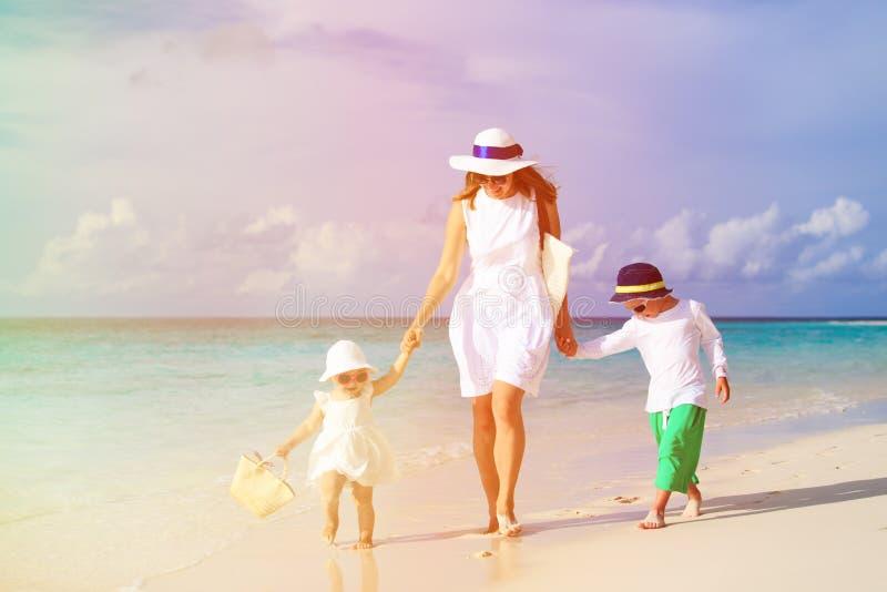 Moeder en twee jonge geitjes die op tropisch strand lopen stock afbeeldingen