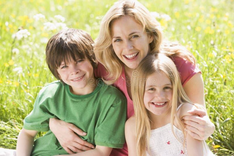 Moeder en twee jonge kinderen die in openlucht zitten royalty-vrije stock afbeelding