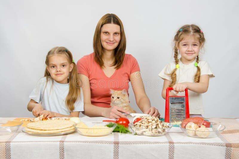 Moeder en twee meisjes bij lijst voorbereide ingrediënten voor de pizza Zij letten op een kat stock afbeelding