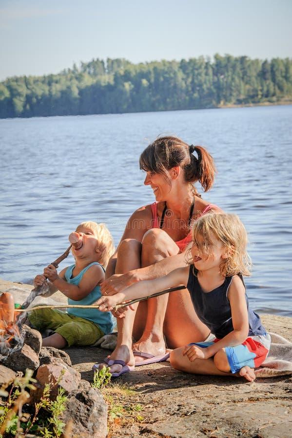 Moeder en twee zonen die worsten roosteren royalty-vrije stock afbeelding