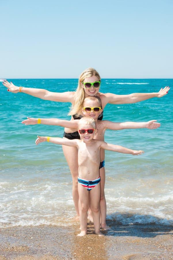 Moeder en twee zonen in zonnebril die en op het strand rusten spelen De vakantie van de de zomerfamilie royalty-vrije stock foto