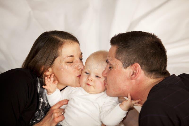 Moeder en vader die hun babymeisje kussen stock foto