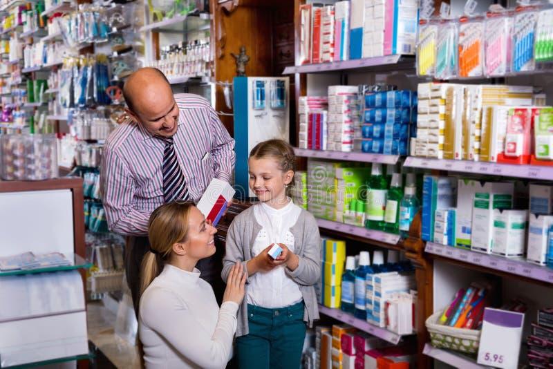 Moeder en vader die met jong geitje een artikel in farmaceutisch s plukken royalty-vrije stock foto's