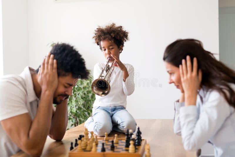Moeder en vader die schaak proberen te spelen terwijl hun kind trompet speelt royalty-vrije stock afbeelding