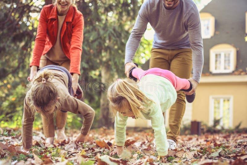 Moeder en vader het spelen met dochters bij huisbinnenplaats royalty-vrije stock afbeelding