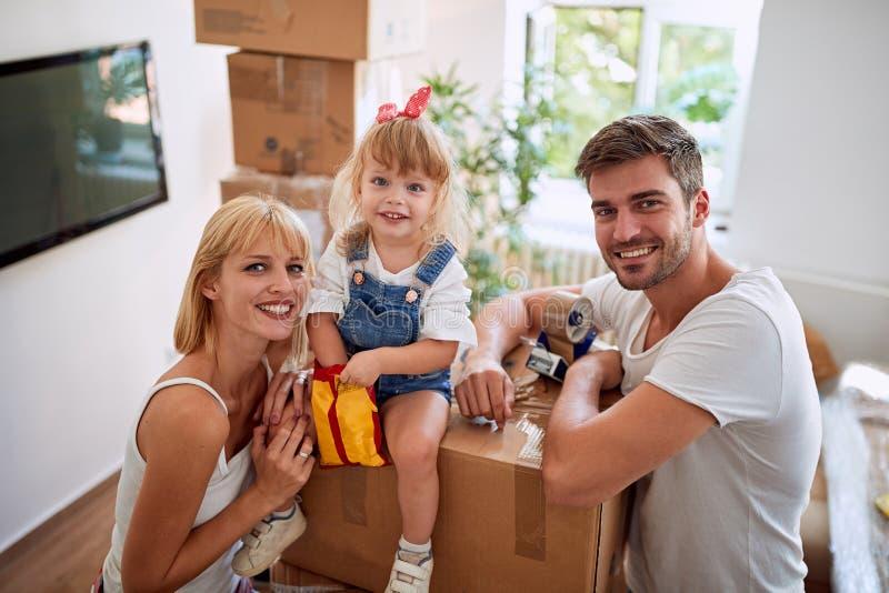 Moeder en vader met een meisje die zich in nieuw huis bewegen stock foto's