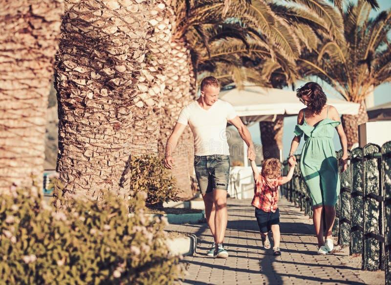 Moeder en vader met zoonsgang bij strandpalmen De zomervakantie van gelukkige familie Liefde en vertrouwen als familiewaarden Kin stock foto