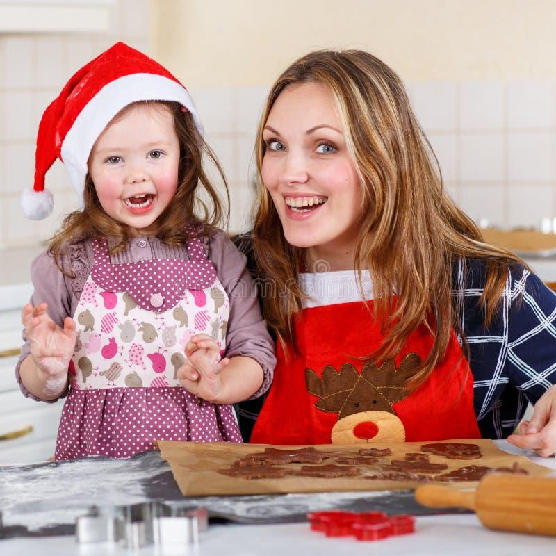 Moeder en van weinig het bakselpeperkoek van het jong geitjemeisje koekjes voor Christus royalty-vrije stock afbeeldingen