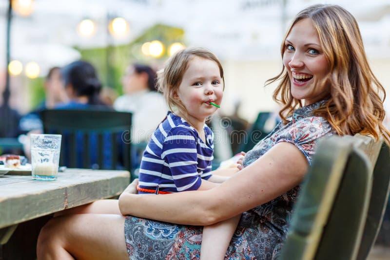 Moeder en weinig aanbiddelijke jong geitjemeisje het drinken koffie in openluchtc royalty-vrije stock foto's