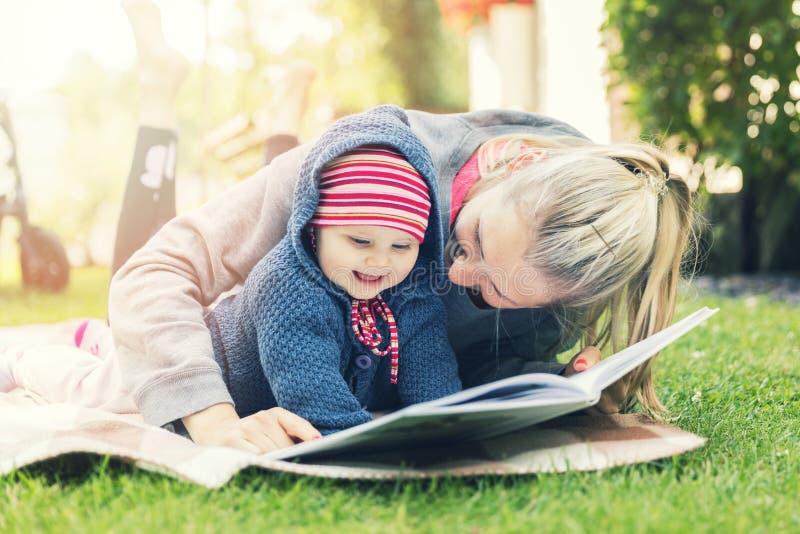 Moeder en weinig de lezingsboek van het babymeisje samen op deken royalty-vrije stock afbeelding