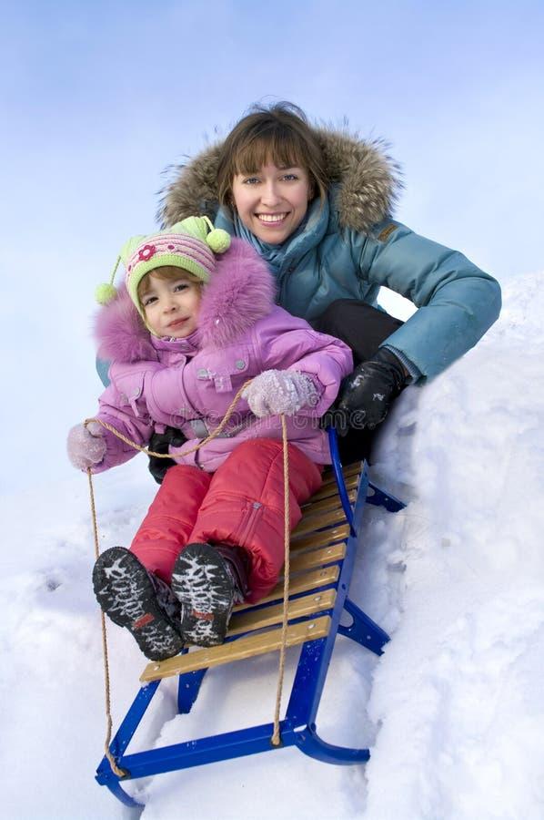 Moeder en weinig dochter die binnen de sneeuw glijden royalty-vrije stock afbeelding