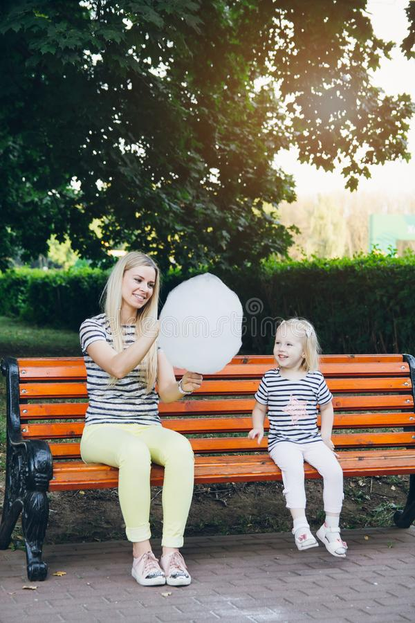 Moeder en weinig dochter die gesponnen suiker eten stock afbeeldingen
