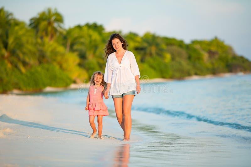 Moeder en weinig dochter die op het strand op de Maldiven bij de zomervakantie lopen royalty-vrije stock afbeeldingen