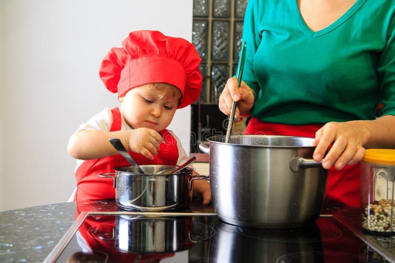 Moeder en weinig dochter het koken in de keuken stock foto