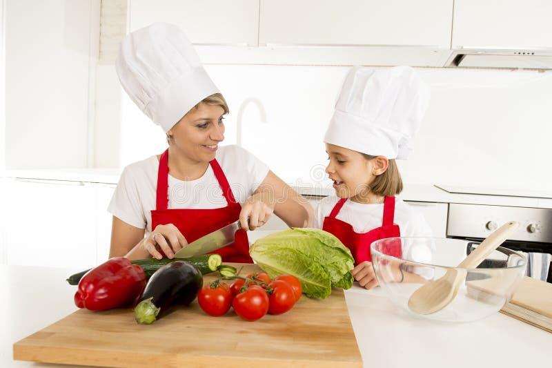Moeder en weinig dochter het koken samen met hoedenschort die salade thuis keuken voorbereiden stock foto's