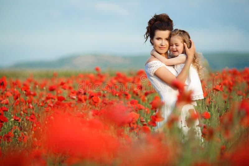 Moeder en weinig dochter op het bloemgebied stock foto's