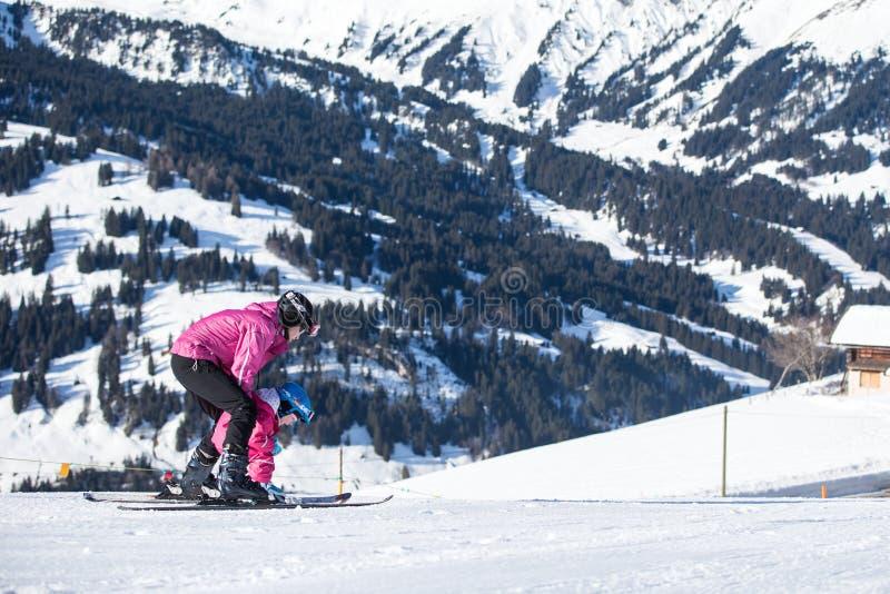 Moeder en weinig kind die in de bergen van Alpen ski?en Actief mamma en peuterjong geitje met veiligheidshelm, beschermende brill stock afbeeldingen