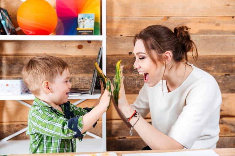 Moeder en weinig zoon die hoogte vijf met geschilderde handen geven stock foto