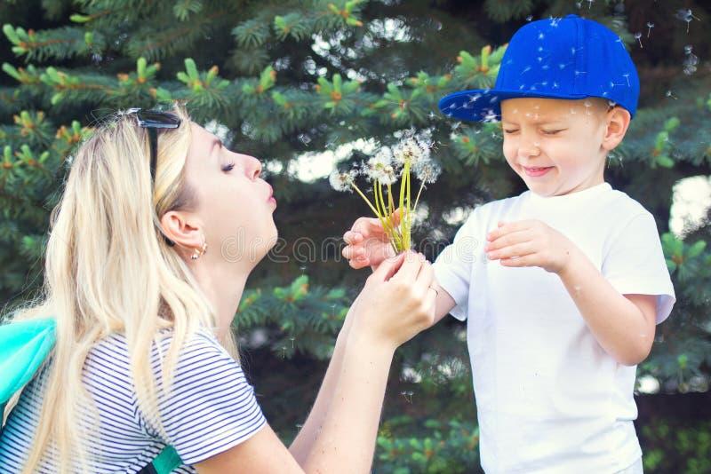 Moeder en weinig zoon die op een paardebloem blazen stock foto's
