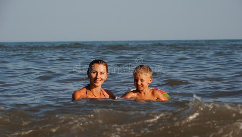 Moeder en zon die in het overzees zwemmen De zomervakantie op het overzeese strand royalty-vrije stock fotografie