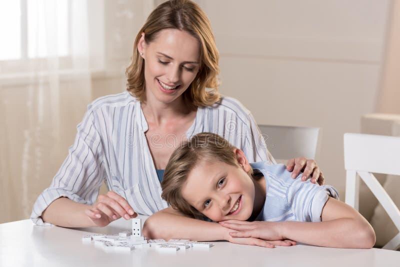 Moeder en zoon bij lijst met dominostukken stock fotografie