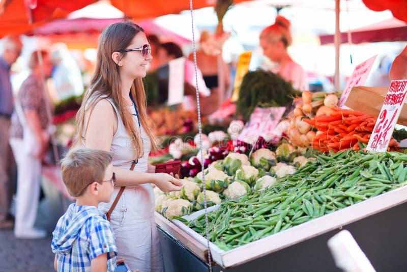 Moeder en zoon bij markt stock afbeelding