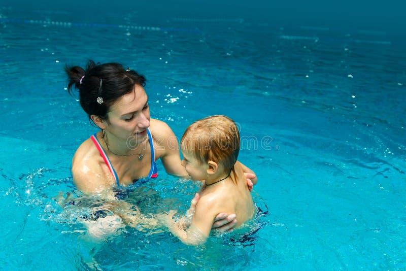 Moeder en zoon in de pool stock foto