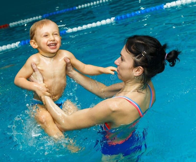 Moeder en zoon in de pool stock fotografie