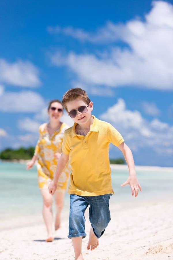 Moeder en zoon die bij strand lopen stock afbeelding