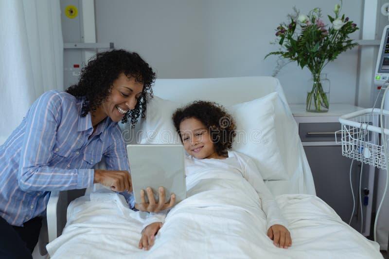 Moeder en zoon die digitale tablet in de afdeling gebruiken bij het ziekenhuis royalty-vrije stock foto