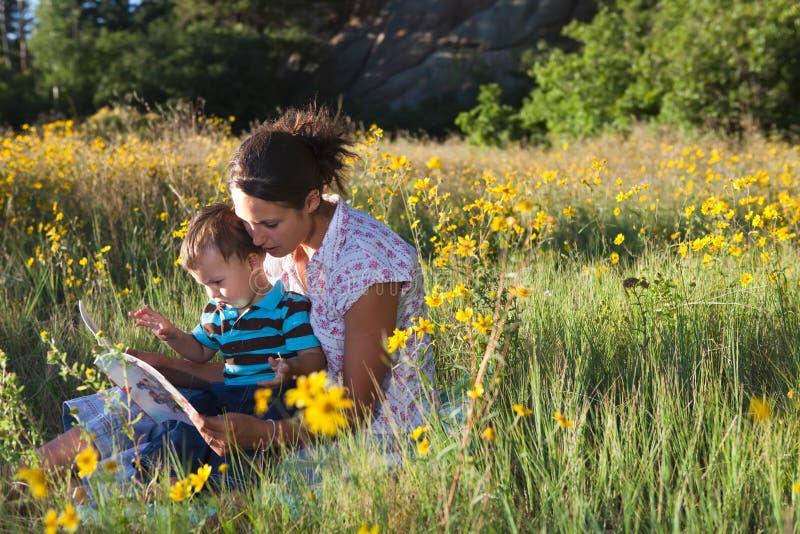 Moeder en zoon die een boek samen lezen stock foto's