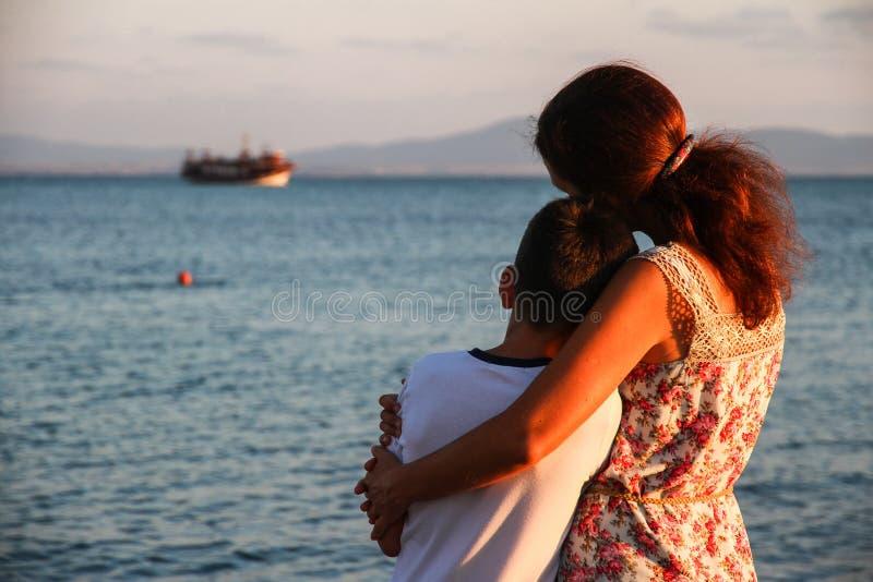 Moeder en zoon die een schip in het overzees bekijken royalty-vrije stock afbeelding