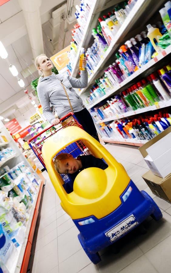 Moeder en zoon die in een supermarkt winkelen royalty-vrije stock afbeeldingen