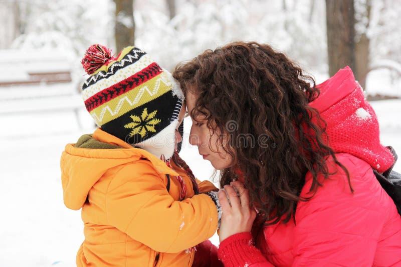 Moeder en zoon die elkaar in de winterpark bekijken stock afbeeldingen