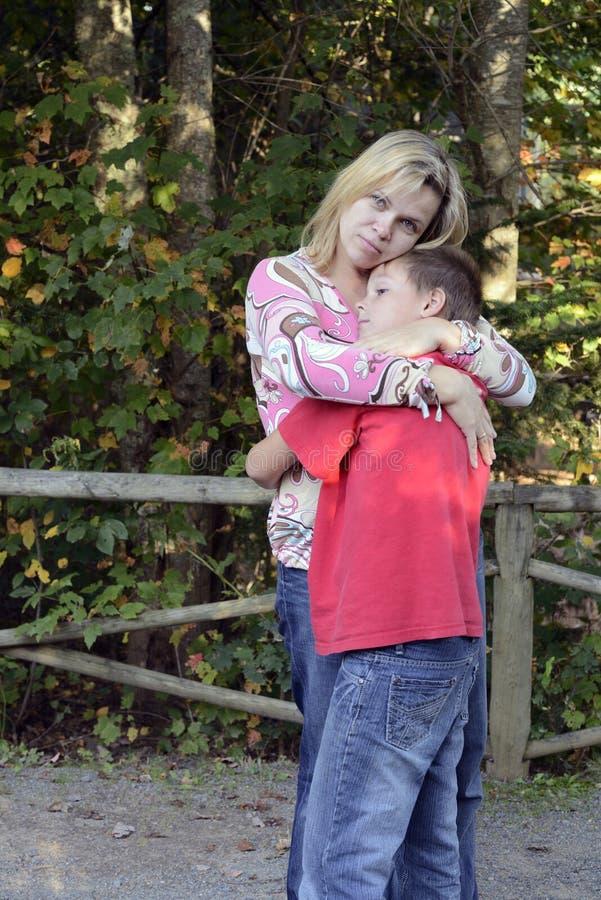 Moeder en zoon die elkaar koesteren stock afbeeldingen