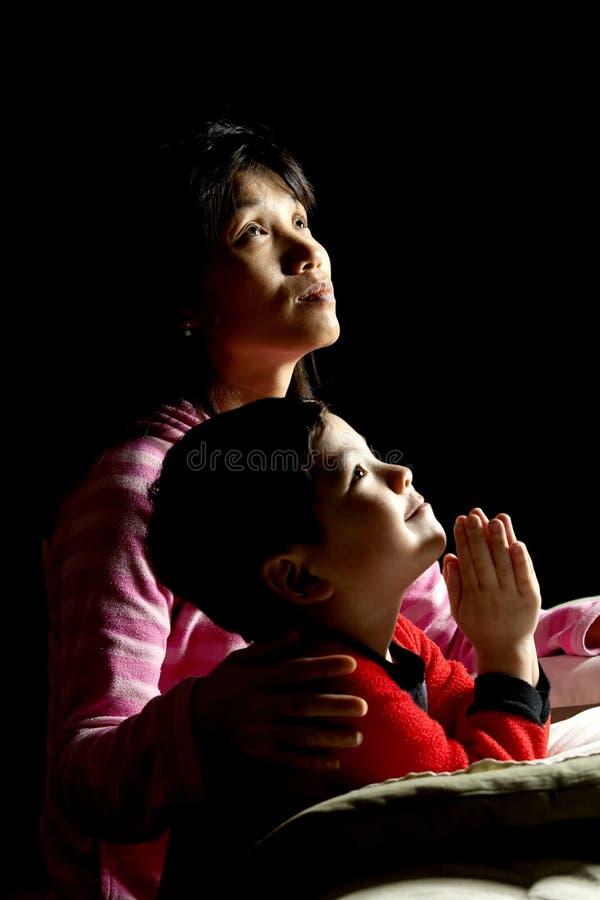 Moeder en zoon die gebeden zeggen. stock fotografie