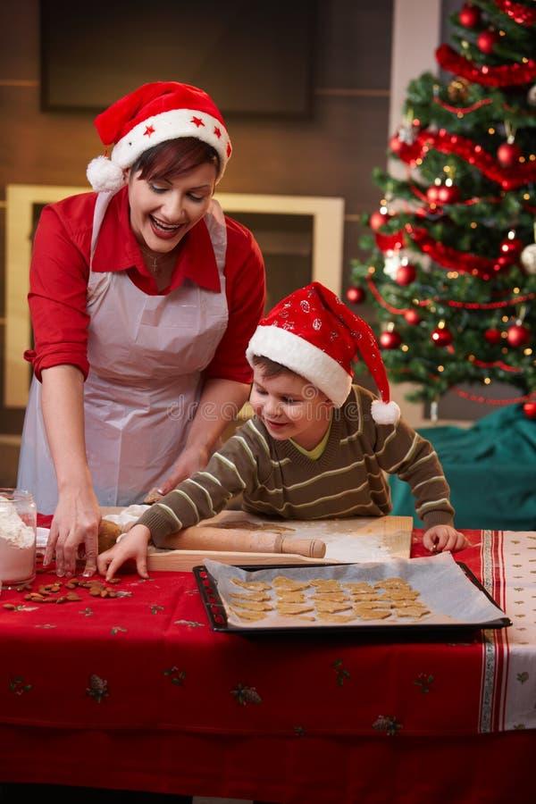 Moeder en zoon die Kerstmiscake maken stock fotografie