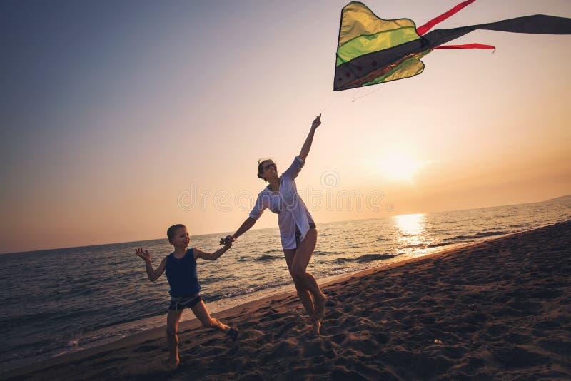 Moeder en zoon die met vlieger op het strand lopen stock afbeelding