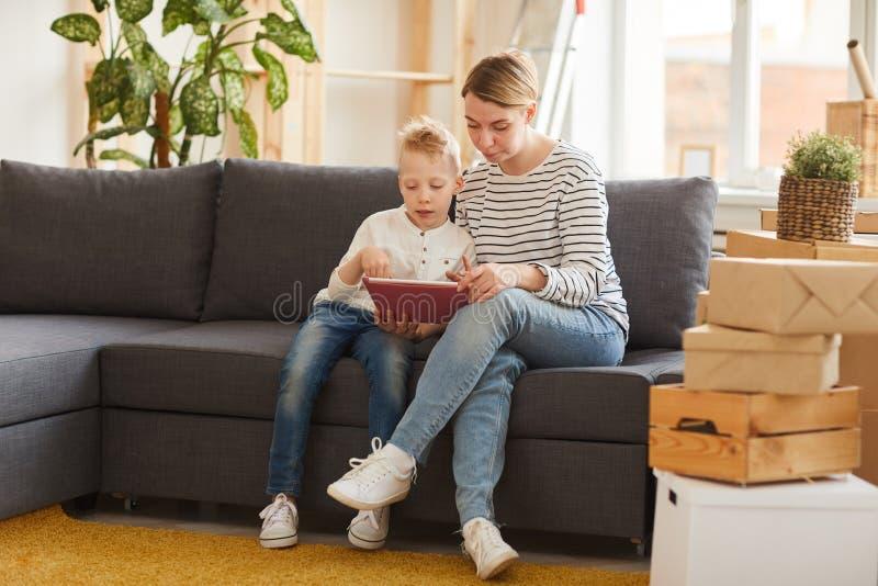 Moeder en zoon die mobiele toepassing op tablet gebruiken stock afbeeldingen