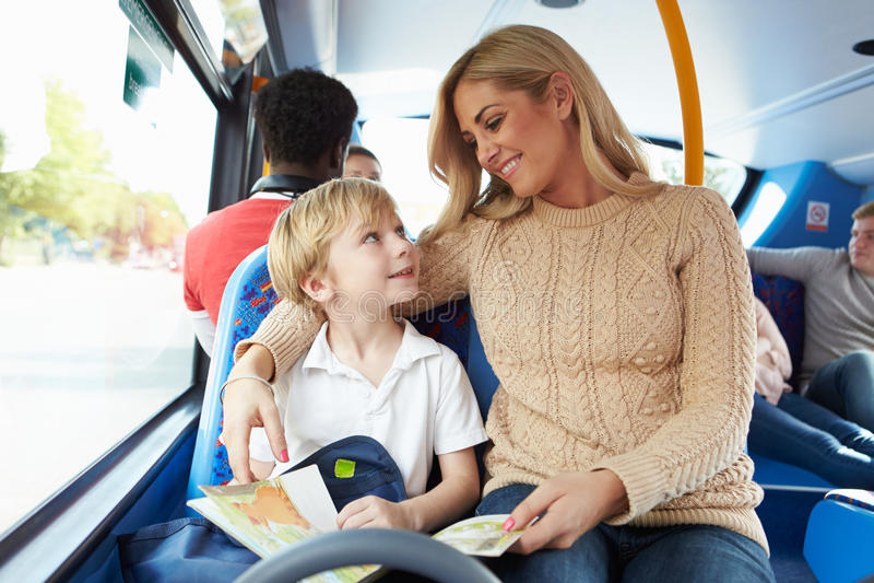 Moeder en Zoon die naar School op Bus samen gaan stock afbeelding