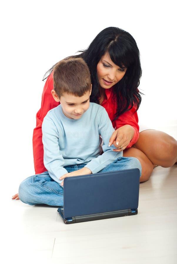 Moeder en zoon die notitieboekje gebruiken stock foto's