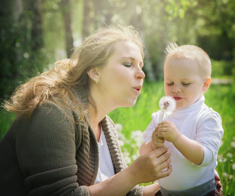 Moeder en zoon die op een paardebloem blazen stock foto