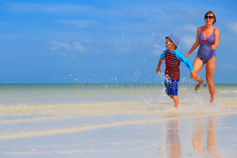Moeder en zoon die op het strand lopen stock fotografie