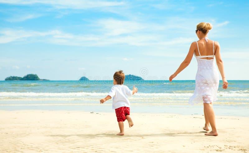Moeder en zoon die op strand lopen stock foto