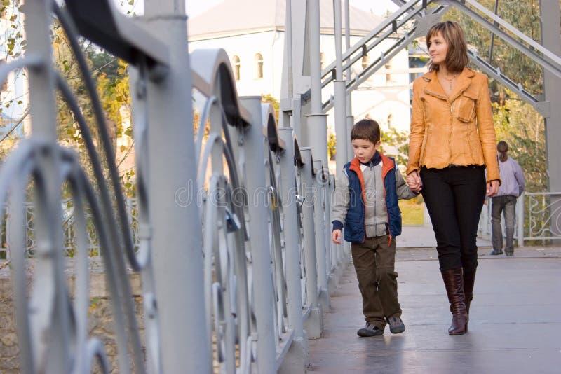 Moeder en zoon die over de brug lopen stock afbeelding