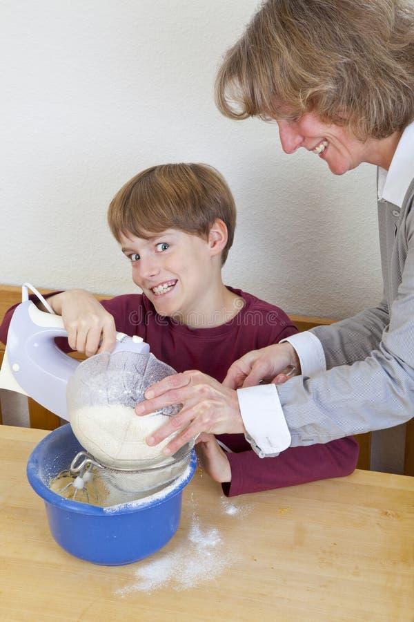 Moeder en zoon die pret in keuken hebben royalty-vrije stock afbeeldingen