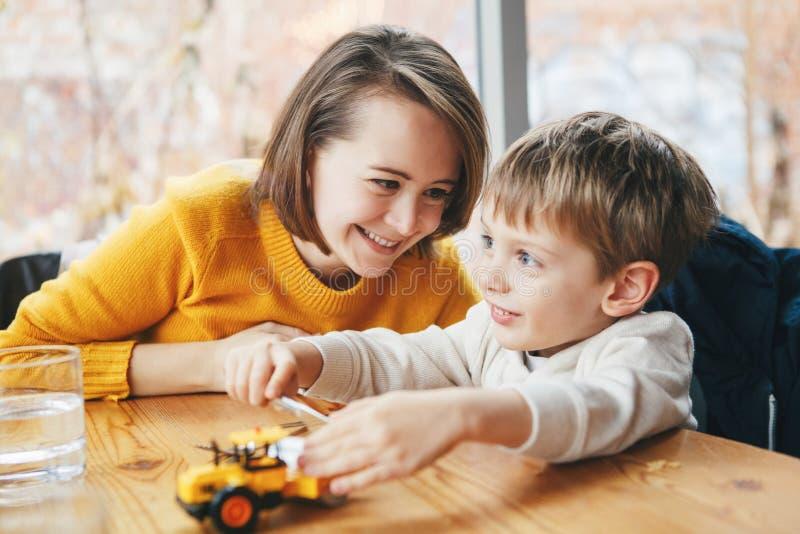 Moeder en zoon, die in restaurantkoffie bij lijst, het glimlachen het spelen met stuk speelgoed auto zitten stock foto's