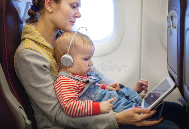Moeder en zoon die tablet aan boord van vliegtuig gebruiken stock afbeelding