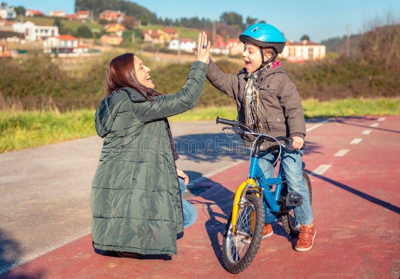 Moeder en zoon die vijf geven door succes te berijden stock afbeelding